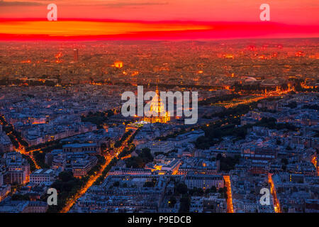 Aerial view of national residence of the Invalids palace on red sunset with night street light from panoramic terrace of Tour Montparnasse. Paris urban skyline cityscape. European capital of France. - Stock Photo