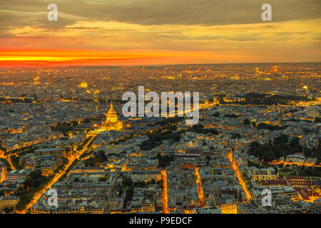Paris urban skyline cityscape. Aerial view of national residence of the Invalids palace on orange sunset with night street light from panoramic terrace of Tour Montparnasse. European capital of France - Stock Photo