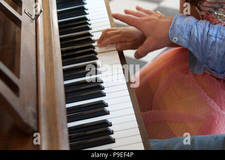 Piano lesson: a adult trying to encourage a child on the piano by example - Stock Photo