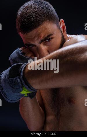 Double arm block. Boxing trainer showing defensive techniques. Combat sport, fight club. - Stock Photo