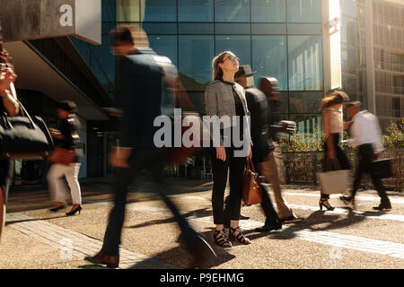 Woman standing amidst a busy office going crowd hooked to their mobile phones. Businesswoman holding her hand bag standing still on a busy street with - Stock Photo