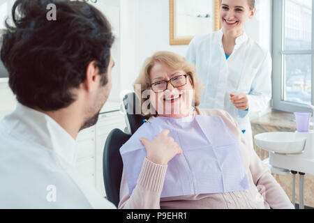 Dentist and assistant greeting senior patient  - Stock Photo
