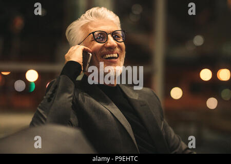Portrait of happy senior businessman talking on mobile phone in office. Mature corporate professional sitting late at night in office and making phone - Stock Photo