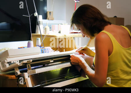 Woman knits on knitting machine at night. Homeworking side job at home. - Stock Photo