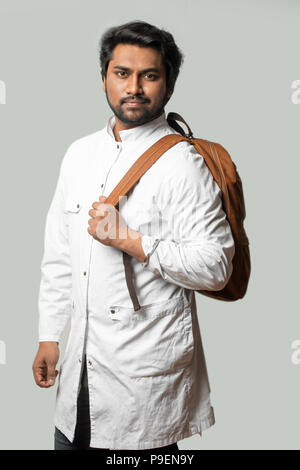 young doctor is going home after working day isolated on the grey background.travel concept. - Stock Photo