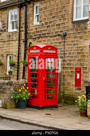 A K6 red telephone box (UK) and wall postbox in Esholt, West Yorkshire, England. - Stock Photo