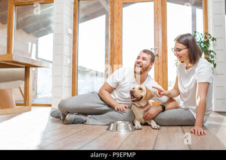 Couple with dog in the house - Stock Photo