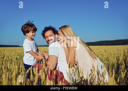 Happy family having fun playing  in the field. - Stock Photo
