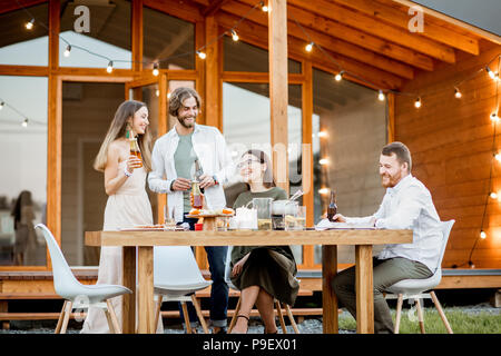 Friends dining on the backyard of the house - Stock Photo