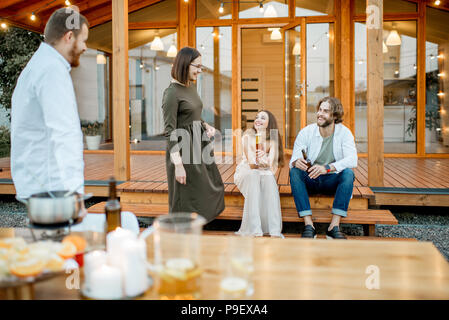 Friends having fun together near the house outdoors - Stock Photo