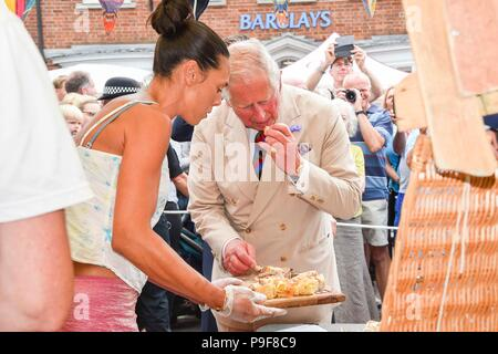 Honiton, Devon, UK.  18th July 2018.   The Duke and Duchess of Cornwall visit the Gate to Plate food market at Honiton in Devon.  Prince Charles tastes some cake at a stall.  Picture Credit: Graham Hunt/Alamy Live News - Stock Photo