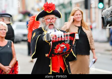 Honiton, Devon, UK.  18th July 2018.   The Duke and Duchess of Cornwall visit the Gate to Plate food market at Honiton in Devon.  Honiton town crier Dave Retter gives a rousing welcome cry.  Picture Credit: Graham Hunt/Alamy Live News - Stock Photo