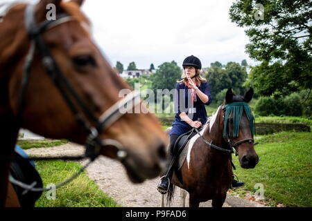 Russia. 18th July, 2018. TULA REGION, RUSSIA - JULY 18, 2018: Katerina Potapova, an American-based great-great-granddaughter of Russian writer Leo Tolstoy, enjoys a horse ride at the Yasnaya Polyana museum-estate in the Tula Region, where his descendants and relatives gather from all over the world ahead of his 190th birthday. Sergei Bobylev/TASS Credit: ITAR-TASS News Agency/Alamy Live News - Stock Photo