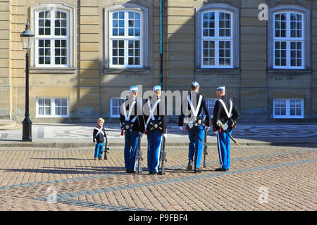 A small boy in a uniform of the Royal Life Guards to the Danish monarchy talking to the real guards at Amalienborg Palace in Copenhagen, Denmark - Stock Photo