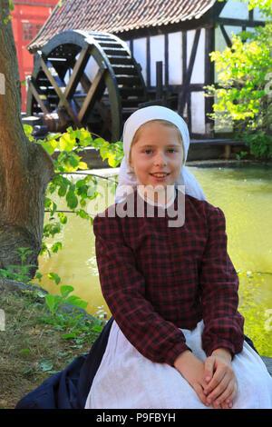 A cute teen farmer girl near a water mill at the open-air town museum Den Gamle By in Aarhus, Denmark - Stock Photo
