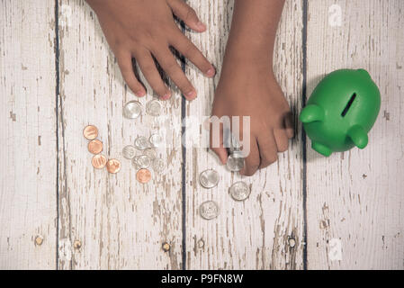 Young boy's hands counting coins from his piggy bank. - Stock Photo
