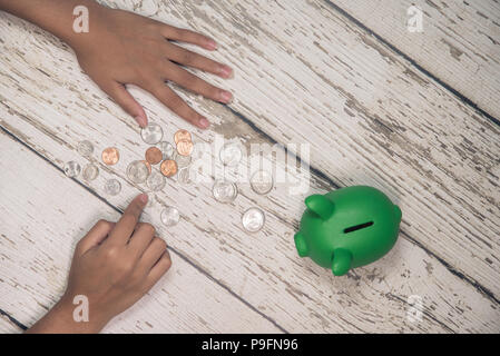Young girls hands counting money from her piggy bank. - Stock Photo