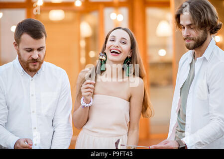Friends having fun on the backyard of the house outdoors - Stock Photo