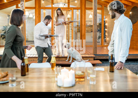 Friends preparing for the dinner near the house - Stock Photo