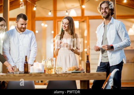 Friends dining near the house - Stock Photo