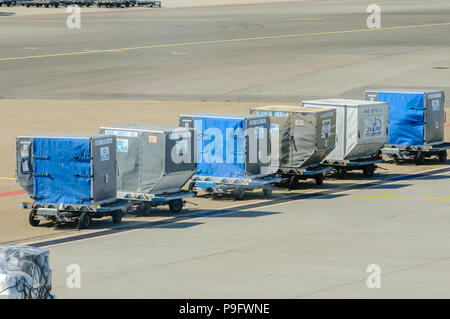 KLM baggage and hold containers on the apron at Schiphol Airport - Stock Photo