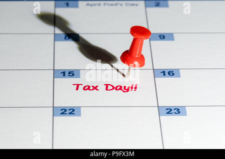 Red pushpin in calendar on April 15th for tax day - Stock Photo