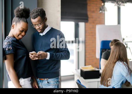young african attractive woman and man standing in the corner of office and looking at the screen of cell phone in the loft office - Stock Photo