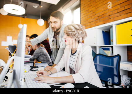 close up portrait of male assistant helping to beautiful manager to use computer in the loft office - Stock Photo