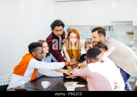 close up image of diverse managers holding hands together in the office kitchen - Stock Photo