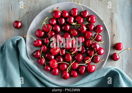 Top view on the gray plate of cherries on rustic wooden background - Stock Photo