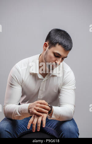 handsome man using his smart watch while sitting on the chair. busy man looking at the watch - Stock Photo