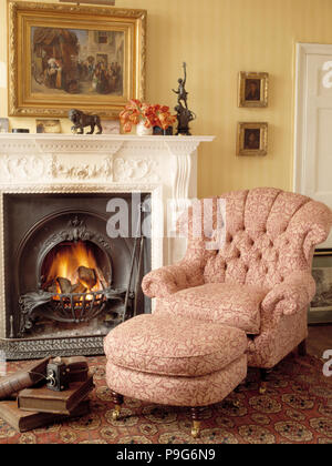 Armchair beside fireplace in traditional living room - Stock Photo
