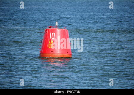 Red beacon buoy with speed limit of ten knots, floating in blue sea or ocean - Stock Photo