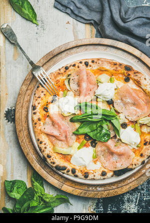 Freshly baked pizza with ham, artichokes, cheese and basil - Stock Photo