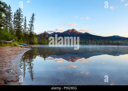 Golden sunrise breaks out over Pyramid Mountain and low fog settles on the surface of Edith Lake in Jasper National Park with reflections off its calm - Stock Photo