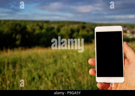 phone in mens hand outdoors - Stock Photo