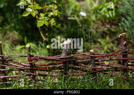Wattle in the green garden. Small Fence made of weaving thin branches - Stock Photo