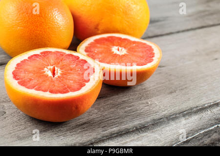 Pink red grapefruit cut in half, with two whole in background on gray wood table. - Stock Photo
