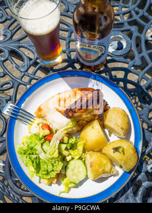Lunch  a quarter roastt chicken eaten outdoors with new potatoes salad and a bottle of Norfolk Bitter beer - Stock Photo