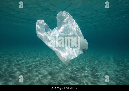 Plastic waste underwater, a plastic bag in the Mediterranean sea between water surface and a sandy seabed, Almeria, Andalusia, Spain - Stock Photo