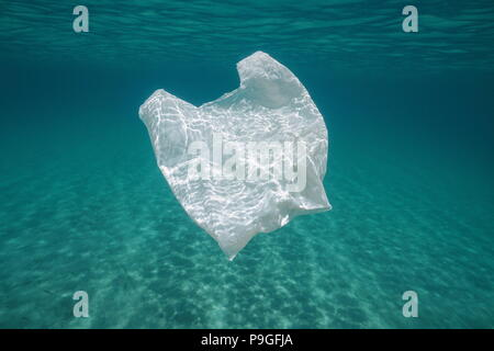 Underwater pollution a plastic bag in the sea between water surface and a sandy seabed, Mediterranean, Almeria, Andalusia, Spain - Stock Photo