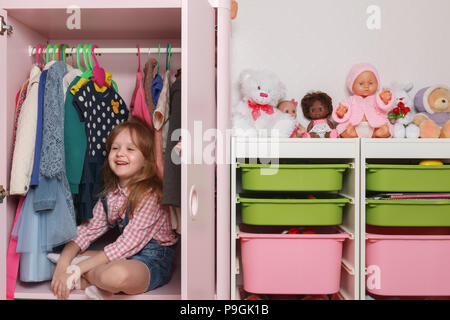 A little girl is sitting in a wardrobe with a children's department. Storage system for children's things - Stock Photo
