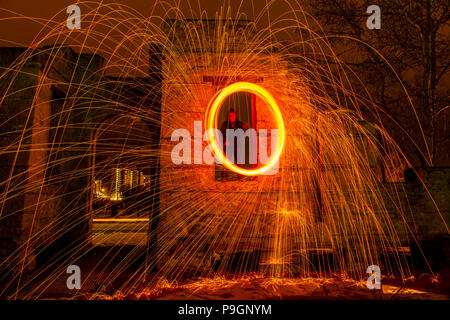 A ring of fire is created from a spinning chunk of burning steel wool on a rope.  A man spins it from a long abandoned stone window. - Stock Photo