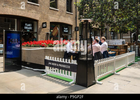 Customers sitting in the Summer Terrace / outdoor seated area at Planet Organic restaurant in Devonshire Square, London, England, UK - Stock Photo