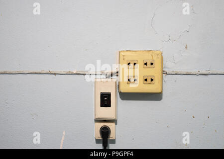 old and dust electricity switches and sockets with wire on grunge blue wall - Stock Photo