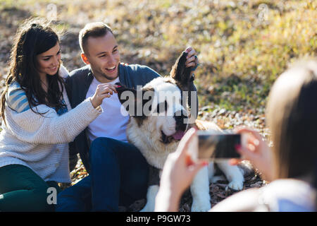 Woman takes a photo of young couple enjoying together with their Saint Bernard puppy . - Stock Photo
