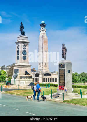 8 June 2018: Plymouth, Devon UK - Couple with two dogs looking at monuments on Plymouth Hoe - left to right, the Armada Monument, the Royal Navy Monum - Stock Photo