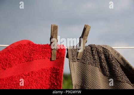 Washing line: red and grey towels hung with sprung wooden pegs on a white nylon coated washing line - Stock Photo