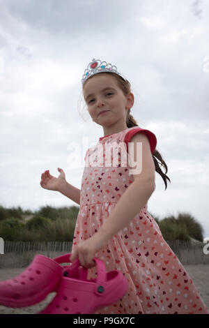 fun shot of a walking 4 year old girl with red long hair wearing a tiara, holding a pair of pink crocs on a beach - Stock Photo