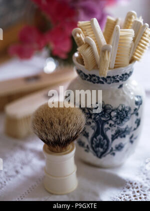Close-up of a vintage badger's hair shaving brush beside a blue and white pot with vintage ivory backed toothbrushes - Stock Photo